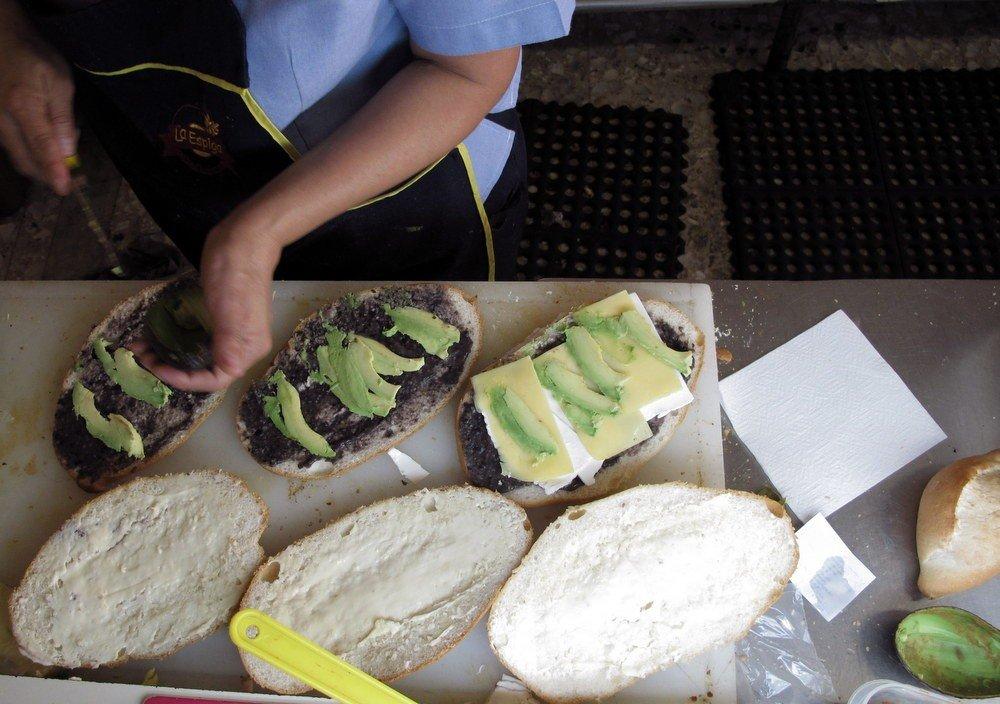 על הלחמניה מורחים חמאה ומוסיפים פריחול'ס ואבוקדו